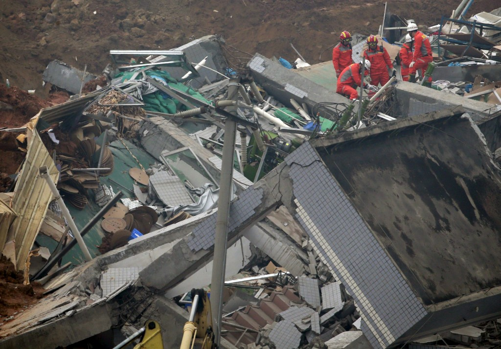 Rescue workers work on a damaged building during search and rescue operations at an industrial estate hit by a landslide in Shenzhen, Guangdong province, December 23, 2015. REUTERS/Kim Kyung-Hoon