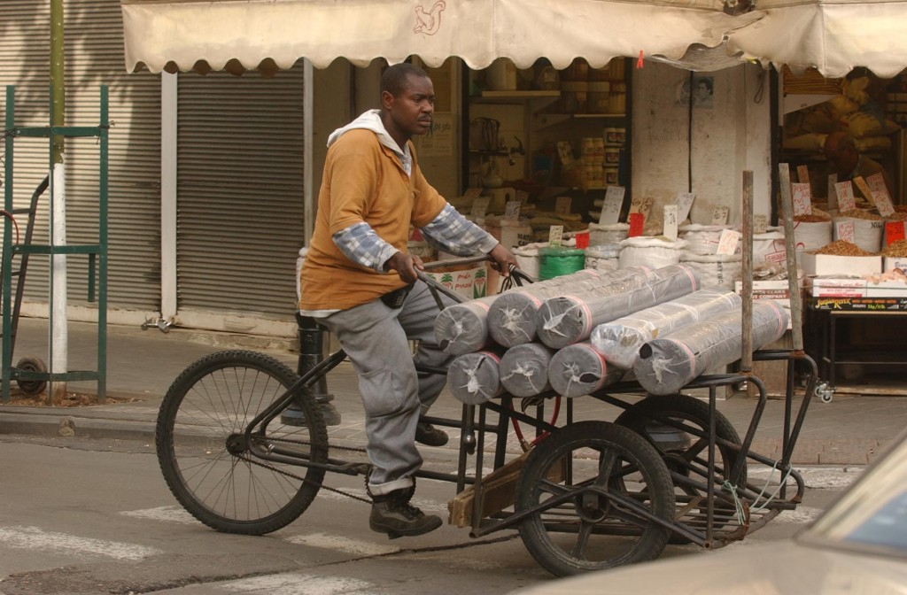 An African laborer rides a bike carrying fabric along a main street in South Tel Aviv on Tuesday, February 12, 2002. Photo by Yossi Zamir/Flash90