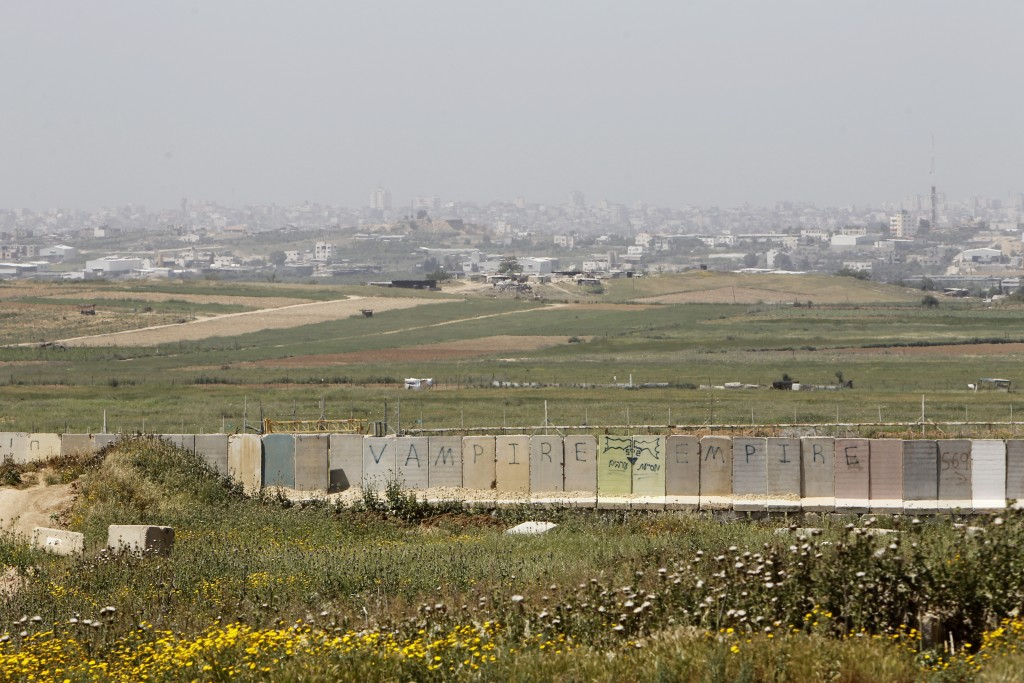 Gaza City seen in the background near the border fence between Israel and Gaza (foreground). Photo by Miriam Alster/FLASH90