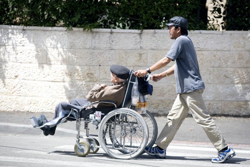 An aide takes care of an elderly Israeli man sitting in a wheelchair. Photo by Abir Sultan/Flash90
