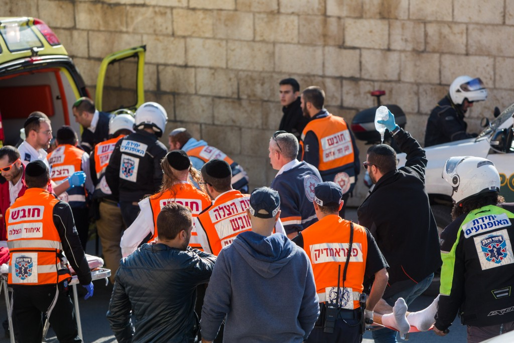 Rescue and medic personnel assist one of the victims of the stabbing at the Old City's Jaffa Gate in Jerusalem on December 23, 2015. Photo by Yonatan Sindel/Flash90