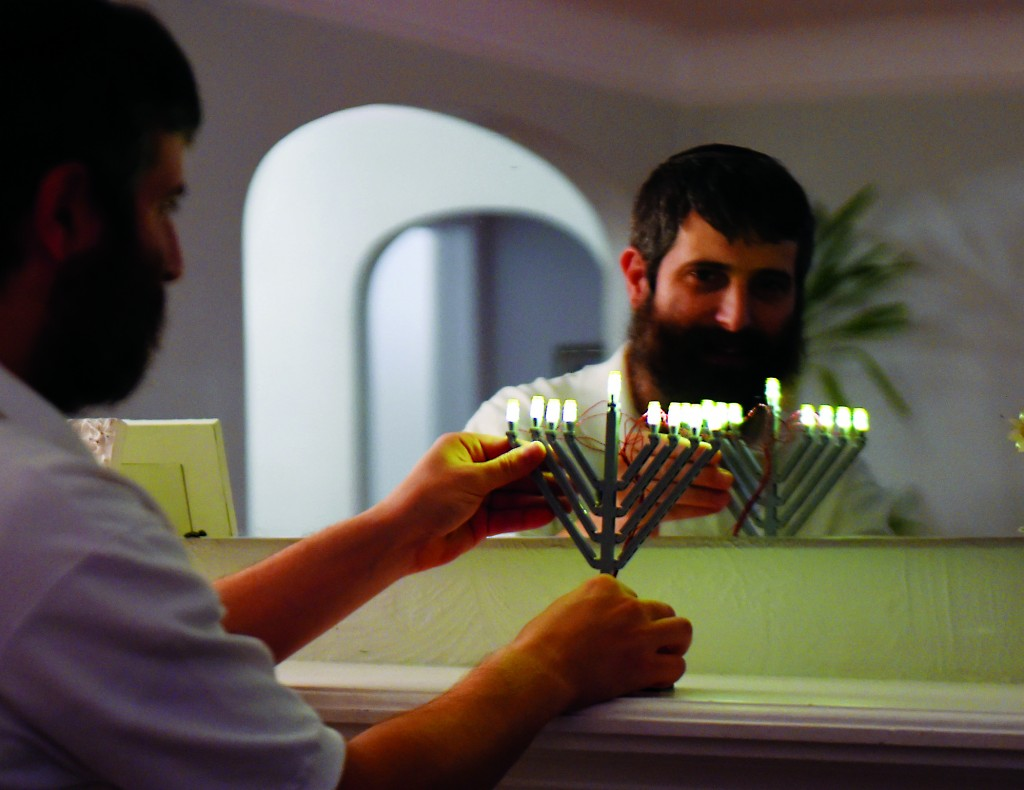 Yitzy Kasowitz places one his LEGO menorahs on the fireplace mantel of his Highland Park home in St. Paul, Minn. on Wednesday, Dec. 2, 2015. The Kasowitz family's year-old business has caught the interest of the world: Jbrick, a St. Paul-based company that makes custom, Jewish-themed LEGO sets. (John Autey/St. Paul Pioneer Press via AP)
