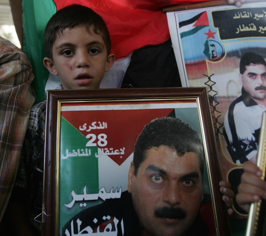 A Palestinian boy holds a framed picture of Lebanese Terroist Samir Kuntar. (Abed Rahim Khatib /Flash90)