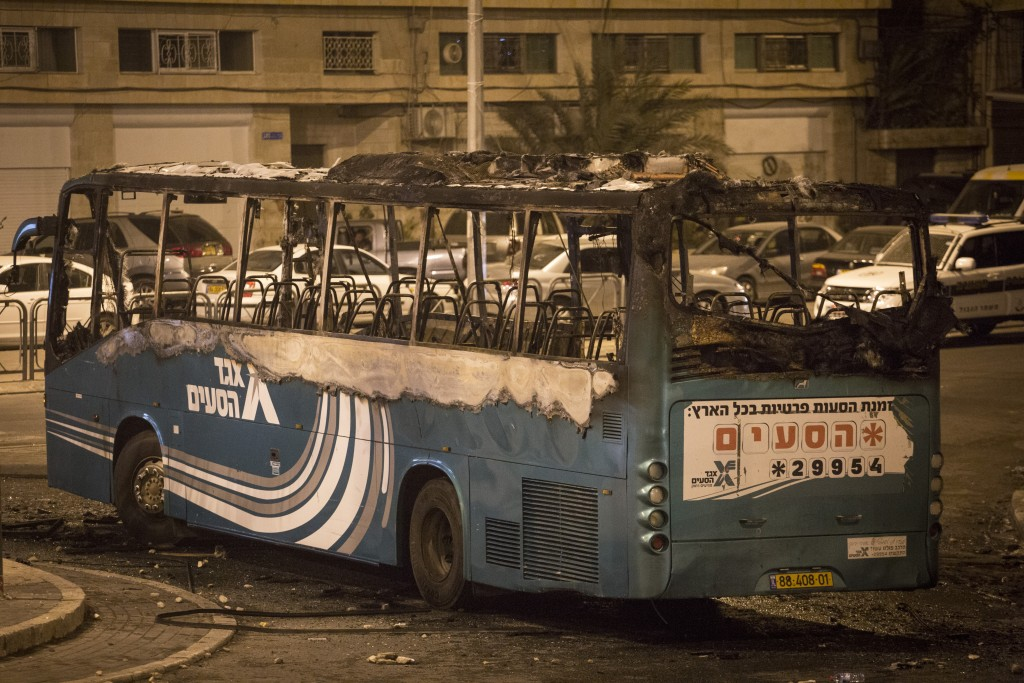 The bus which caught fire from molotov cocktails at a roundabout in the East Jerusalem neighborhood of Ras al Amud, near Mount of Olives, on September 17, 2015. A bus driver took a wrong turn, got into the Palestinian neighborhood and his bus was attacked by molotov cocktails. The bus was empty of passengers and the driver left the bus before it caught fire, unharmed. Photo by Hadas Parush/Flash90