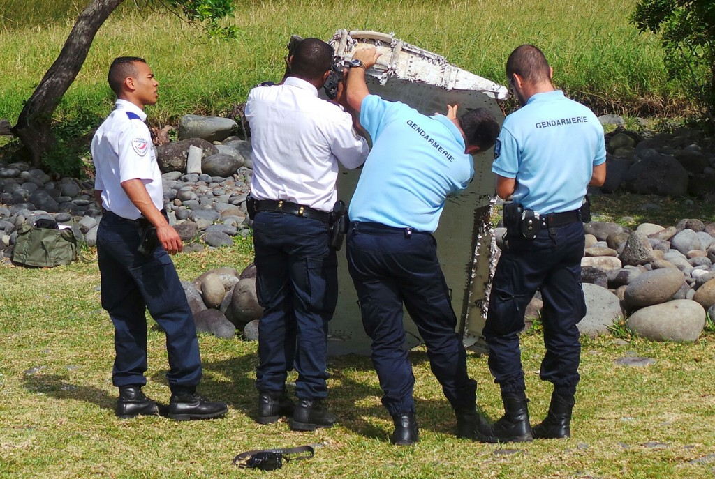 French gendarmes and police inspect a large piece of plane debris which was found on the beach in Saint-Andre, on the French Indian Ocean island of La Reunion, July 29, 2015. France's BEA air crash investigation agency said it was examining the debris, in coordination with Malaysian and Australian authorities, to determine whether it came from Malaysia Airlines Flight MH370, which vanished last year in one of the biggest mysteries in aviation history. Picture taken July 29, 2015. REUTERS/Zinfos974/Prisca Bigot (Newscom TagID: rtrlseven213274.jpg) [Photo via Newscom]