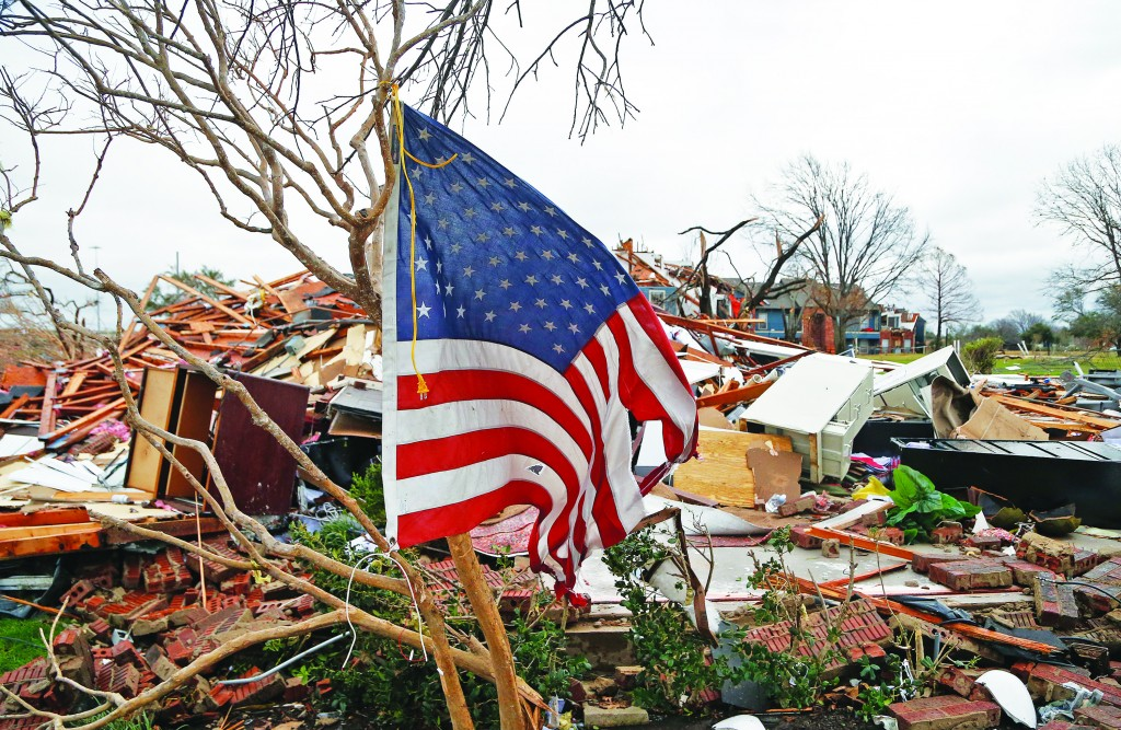 A tattered U.S. flag that had been attatched to a tree waves over the debris at the Landmark at Lake Village North Apartments as the recovery process begins following tornadoes which hit the area late Saturday night December 28, 2015 in Garland, Texas. A meteorolocical assault of tornadoes, blizzards and heavy rain have left dozens dead and a large path of property damage in the Central, U.S. (Photo by Stewart F. House/Getty Images)