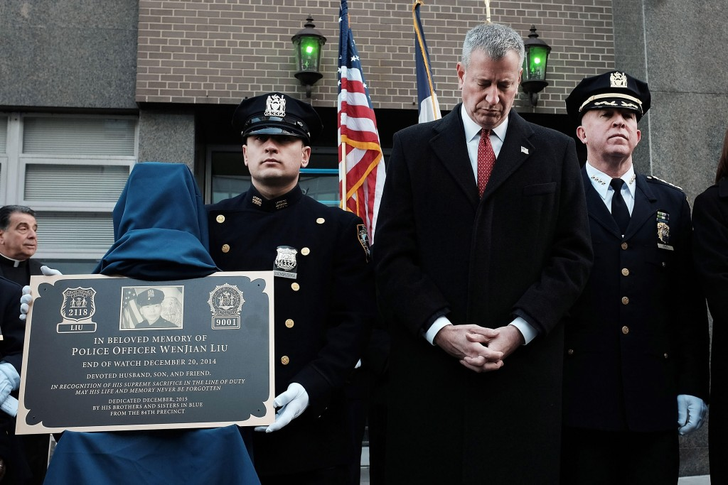New York City Mayor Bill de Blasio bows his head during a plaque dedication ceremony for fallen NYPD officers  Rafael Ramos  and Wenjian Liu at the 84th Precinct in Brooklyn on Sunday. (Photo by Spencer Platt/Getty Images)