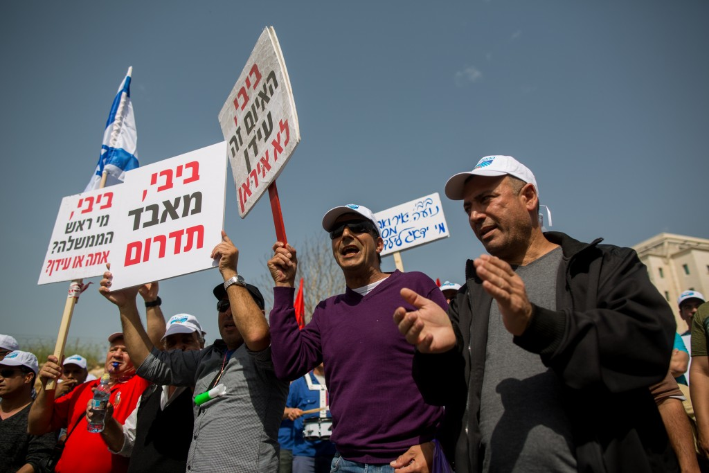 Protesters hold placards as they take part at a labor demonstration outside the Prime Minister's office in Jerusalem on March 11, 2015. Photo by Yonatan Sindel/Flash90