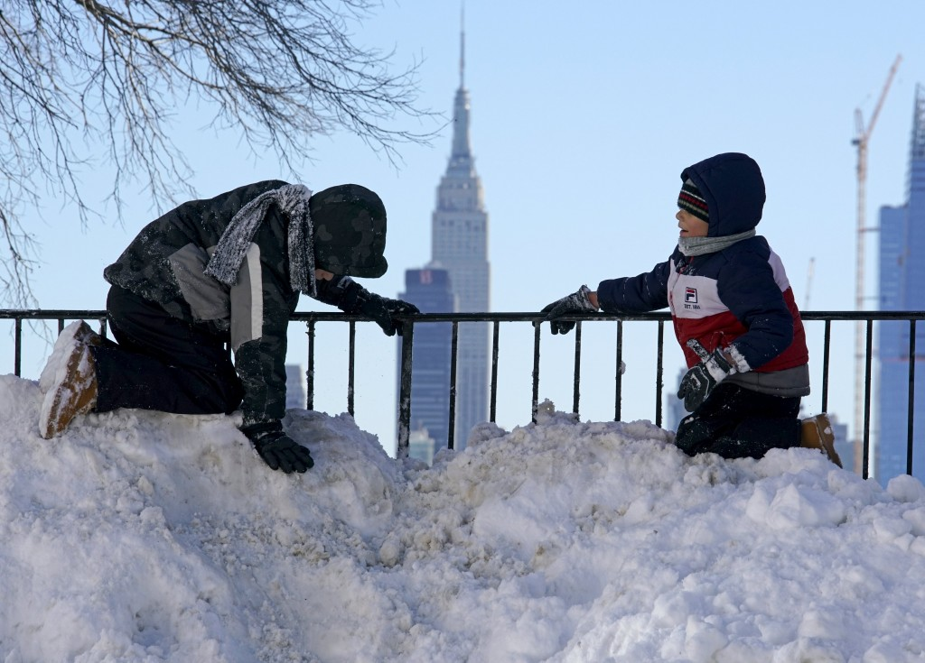 Two boys play atop a pile of snow at the end of a street in Union City, New Jersey, across the Hudson River from Midtown Manhattan on Sunday. (Rickey Rogers/Reuters)