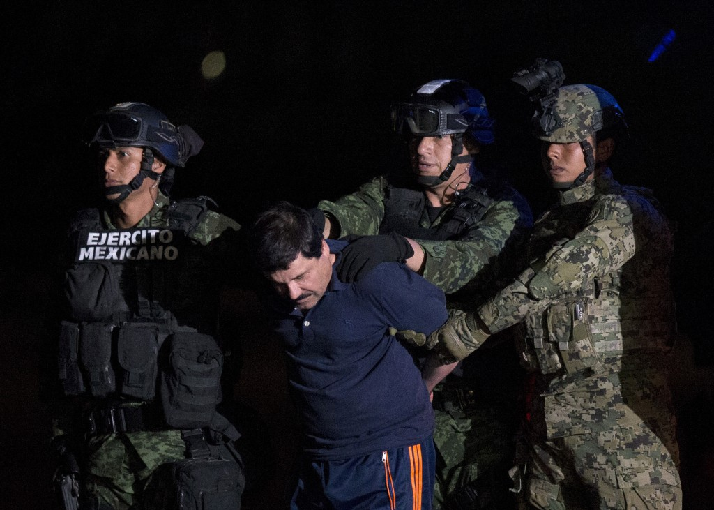 """Mexican drug lord Joaquin """"El Chapo"""" Guzman is escorted by soldiers to a waiting helicopter at a federal hangar in Mexico City on Friday. (AP Photo/Rebecca Blackwell)"""
