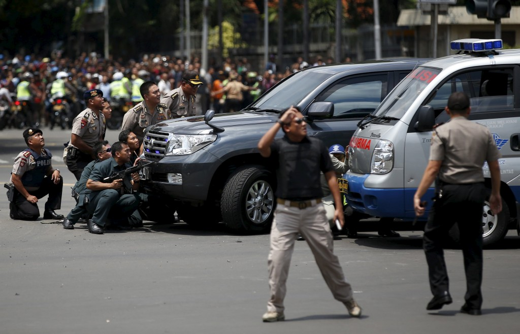 Police officers react near the site of a blast in Jakarta, Indonesia. (Darren Whiteside/Reuters)