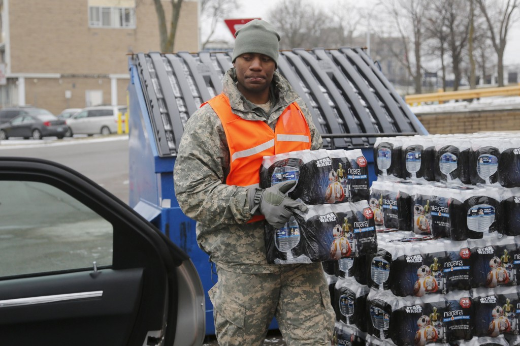 Michigan National Guard member David Brown helps to distribute water to a line of residents in their cars in Flint, Michigan January 21, 2016.      (Rebecca Cook/Reuters)