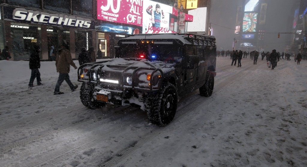 A U.S. Army SUV makes its way down 7th Avenue during a snow storm in Times Square, January 23, 2016. (Carlo Allegri/Reuters)