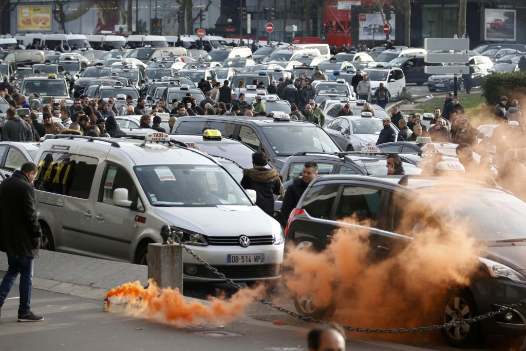 Striking French taxi drivers block traffic Tuesday as they demonstrate at Porte Maillot in Paris during a national protest about competition from private car ride firms like Uber. (Reuters/Charles Platiau)