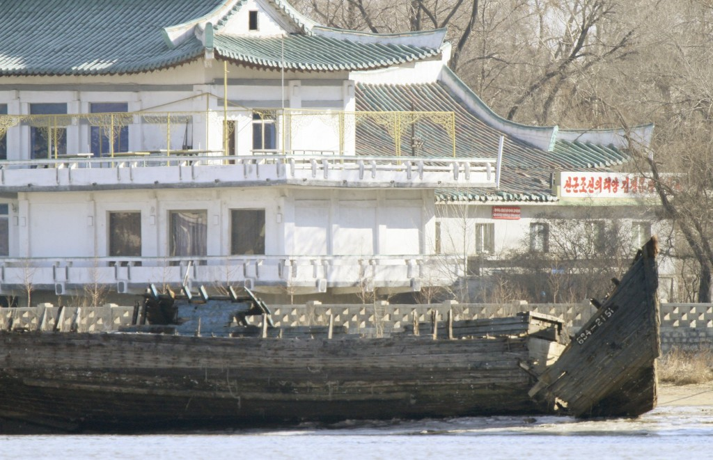 """A deserted boat is seen in front of a building, on the banks of the Yalu River, near the North Korean town of Sinuiju, opposite the Chinese border city of Dandong, January 10, 2016. The characters on the building is partially read, """"North Korea's Sun Kim Jung Un"""". REUTERS/Jacky Chen"""