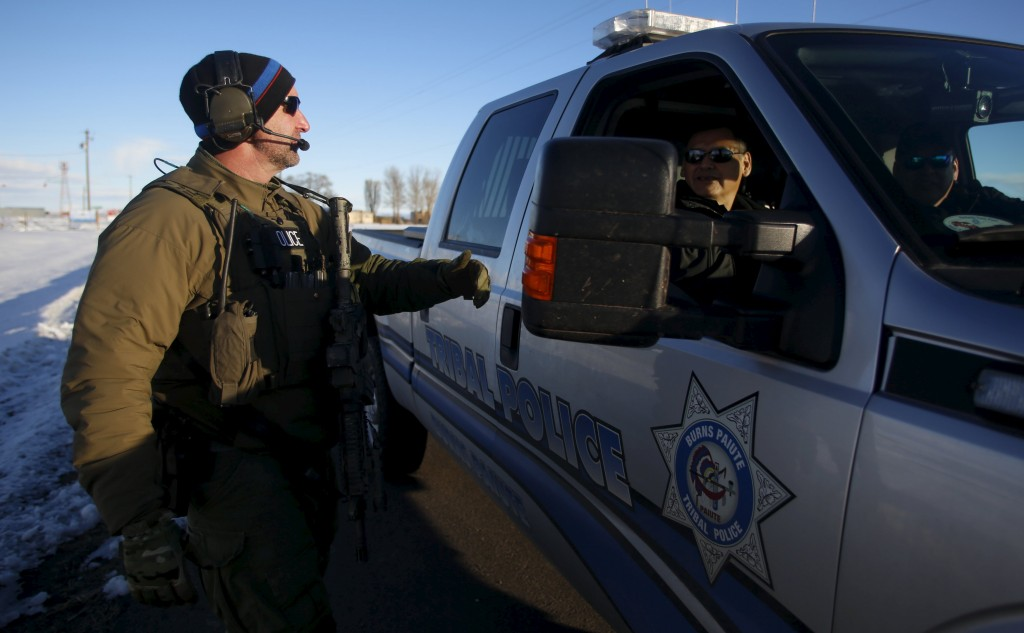 An FBI agent, left, talks to members of the Burns Paiute Tribal Police at the entry to the Burns Municipal Airport in Burns, Oregon January 30, 2016. (Jim Urquhart/Reuters)
