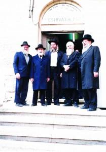 Harav Shmuelevitz (2nd R) at the entrance to Yeshivas Mir. Harav Aaron Chodosh, the Mashgiach, is on the right.