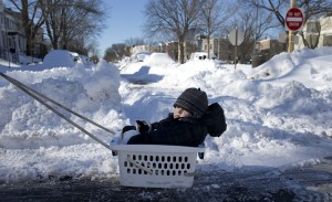 Eli Bokor, 2, is pulled in a laundry basket by his father, Ben Bokor, down a snow-covered 15th Street in southeast Washington, Sunday. (AP Photo/Carolyn Kaster)