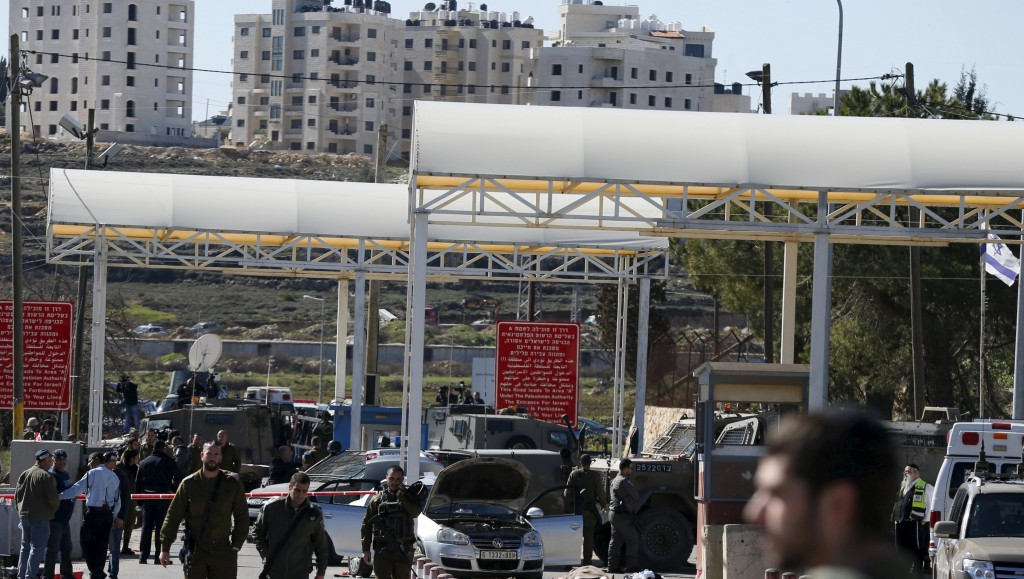 Israeli troops inspect the scene of a shooting attack at an Israeli checkpoint near the West Bank city of Ramallah January 31, 2016. REUTERS/Ammar Awad TEMPLATE OUT