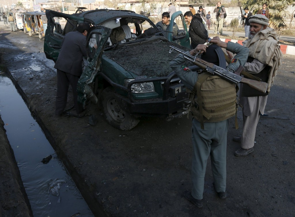 Afghan security personnel stand next to a damaged police vehicle after a blast near the Pakistani consulate in Jalalabad, Afghanistan January 13, 2016. Afghan security forces exchanged fire with gunmen barricaded in a house near the Pakistan consulate in the eastern city of Jalalabad on Wednesday after a suicide bomber blew himself up, officials said. REUTERS/ Parwiz