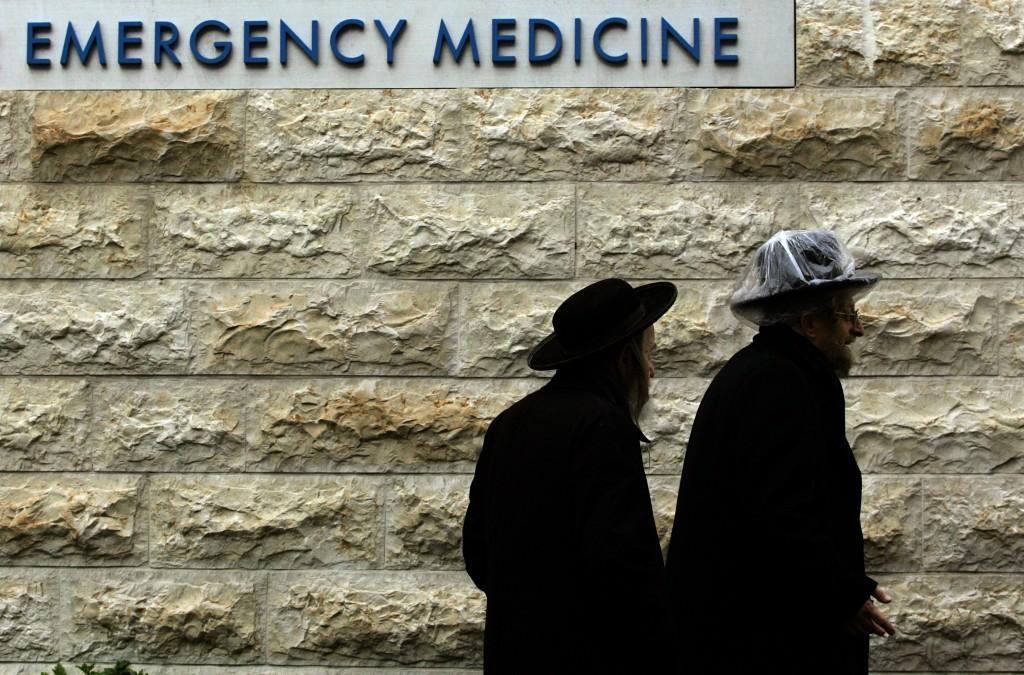 Jewish men walk in the rain toward the Hadassah hospital in Yerushalayim.(AP Photo/Emilio Morenatti)