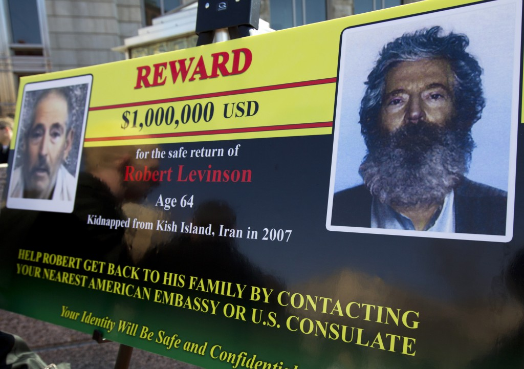 An FBI poster at a 2012 news conference, five years after Robert Levinson was kidnapped. The poster shows (L) an image taken from the video released by his kidnappers, and (R) how he would look like in 2012 after five years in captivity. (AP Photo/Manuel Balce Ceneta)