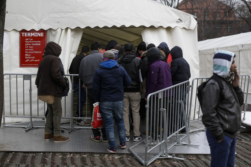Migrants enter a tent that serves as a waiting room at the central registration center for refugees and asylum seekers in Berlin last week. (AP Photo/Markus Schreiber)