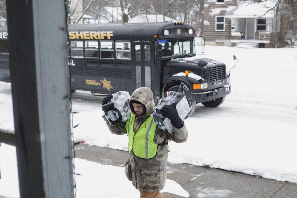 Volunteers going door to door in Flint neighborhoods distributing water filters, replacement cartridges and bottled water on Tuesday. (Conor Ralph/MLive.com- The Flint Journal via AP)