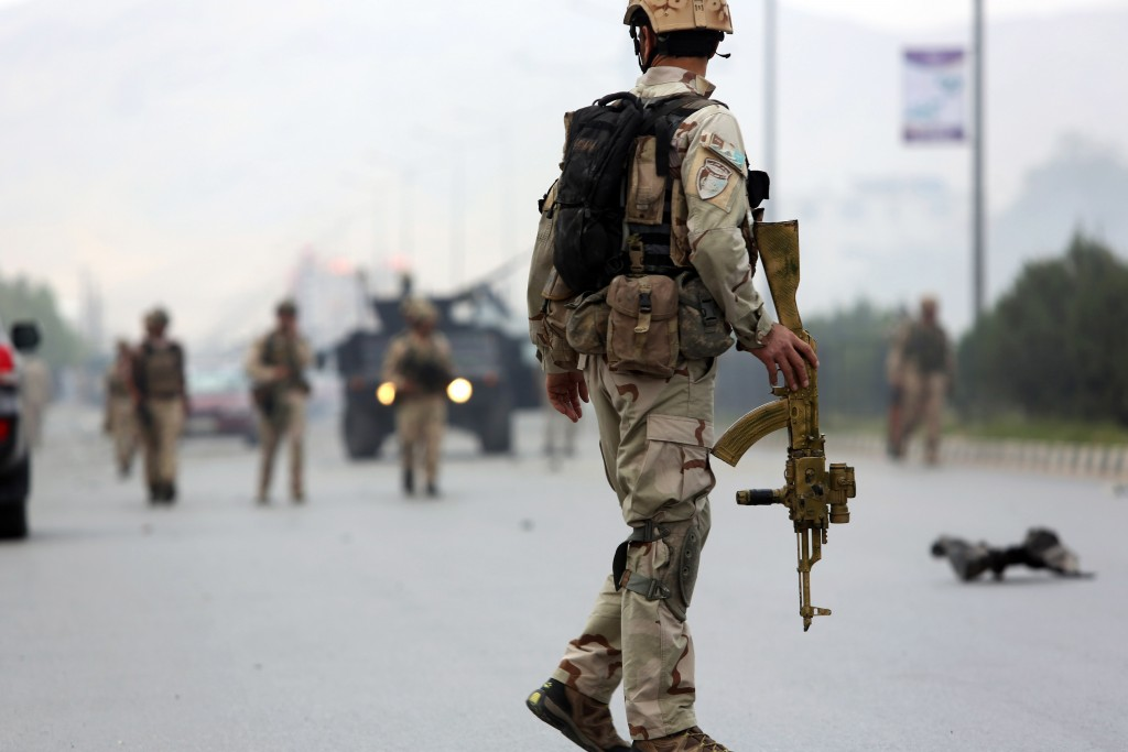 """FILE - In this Monday, June 22, 2015, file photo, Afghan security forces gather at the site of a suicide attack after clashes with Taliban fighters in front of the Parliament, in Kabul, Afghanistan. Afghan forces are struggling to man the front lines against a resurgent Taliban, in part because of untold numbers of """"ghost"""" troops who are paid salaries but only exist on paper. (AP Photo/Rahmat Gul, File)"""