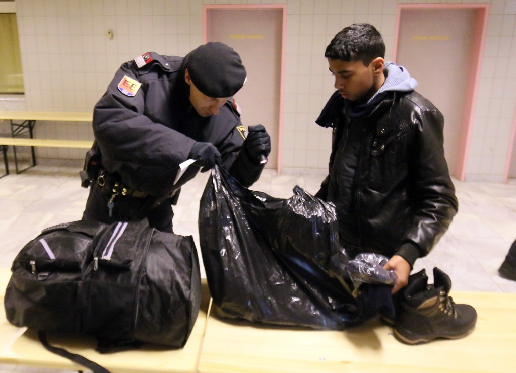 An Austrian police officer checks the luggage of a migrant arriving from Slovenia at a checkpoint at the Karawanks tunnel near Villach, Austria, Wednesday, Jan. 13, 2016. (AP Photo/Ronald Zak)