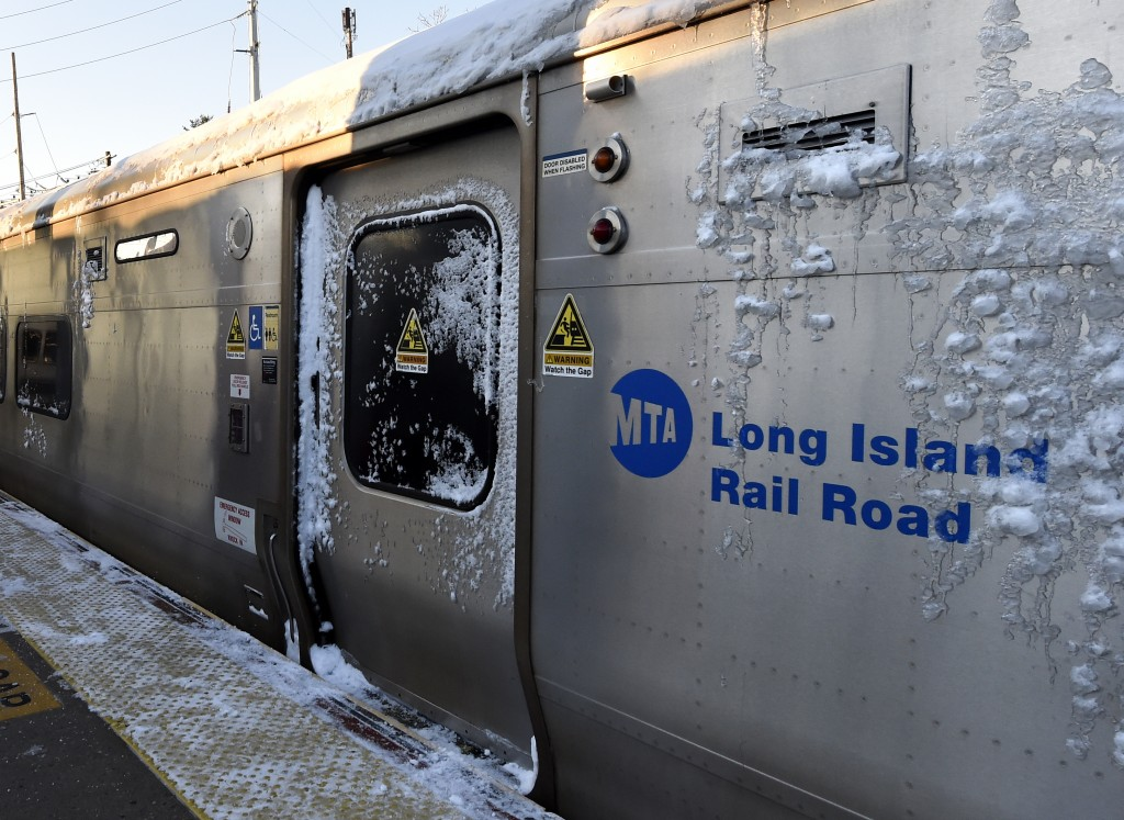 At the Port Washington branch of the Long Island Railroad, a train covered in snow stands still during the morning rush hour as service is suspended on the Port Washington branch due to the recent snowstorm on Monday, Jan. 25, 2016 in Port Washington, N.Y. (AP Photo/Kathy Kmonicek)