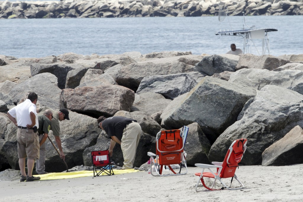 In this July 11, 2015, file photo, authorities investigate a blast that threw a woman into a nearby jetty at Salty Brine beach in Narragansett, R.I. Scientists determined that the explosion was probably caused by the combustion of hydrogen that had built up around the cable. (Steve Szydlowski/Providence Journal via AP, File)