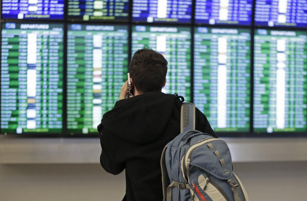 A traveler speaks on the phone as he views the arrival and departure board Friday, Jan. 22, 2016, at San Francisco International airport in San Francisco. (AP Photo/Ben Margot)