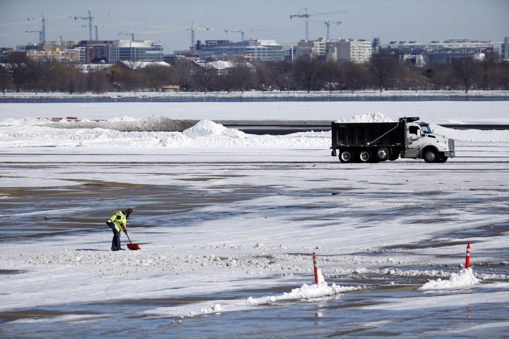 Snow removal is underway on the tarmac at Ronald Reagan National Airport, with the U.S. Capitol dome seen behind, Sunday, Jan. 24, 2016 in Arlington, Va. (AP Photo/Alex Brandon)