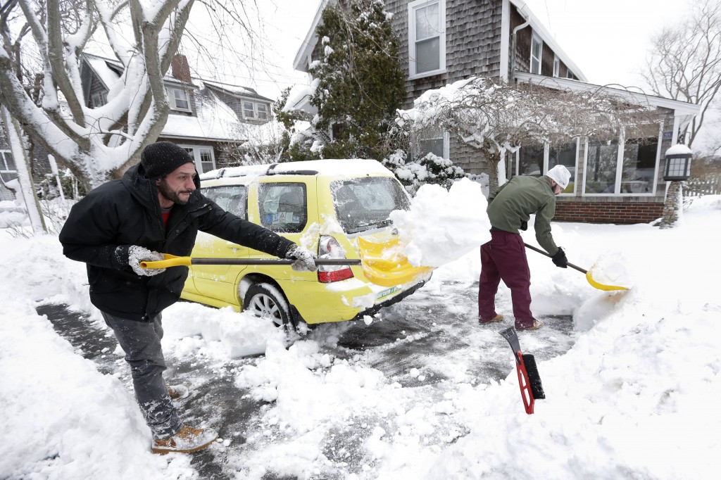 Nicholas Vecchione, left, and Shaun Lewis, right, both of Falmouth, Mass., shovel out a neighbor's car, Sunday, Jan. 24, 2016. (AP Photo/Steven Senne)