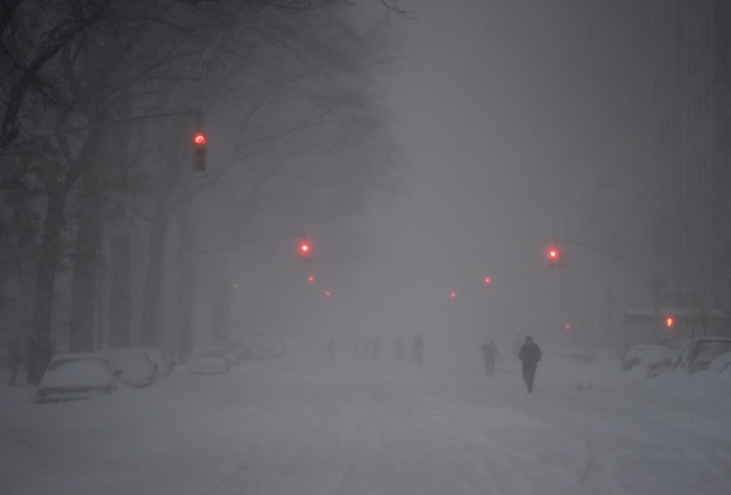 Pedestrians walk along the center of Central Park West in New York Saturday, Jan. 23, 2016, as a large winter storm enveloped the East Coast. Earlier in the afternoon, all non emergency traffic was banned from New York City streets. (AP Photo/Craig Ruttle)