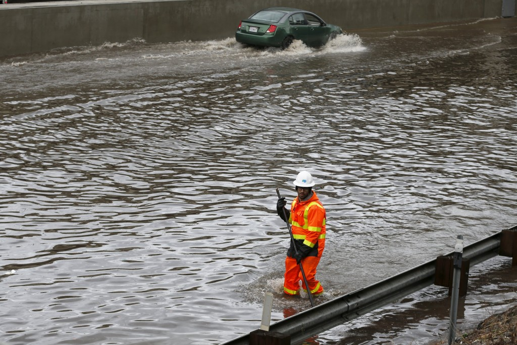 A worker wades through the flooded 5 freeway after an El Nino-strengthened storm brought rain to Los Angeles, California, United States, January 6, 2016. REUTERS/Lucy Nicholson