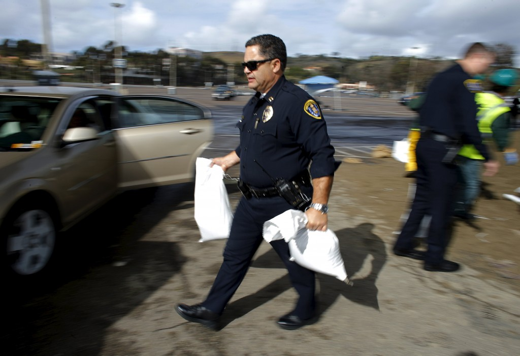 San Diego police officers help load sand bags into civilians vehicles as the city helps residents deal with El Niño-strengthened storms in San Diego,California January 7, 2016.REUTERS/Mike Blake