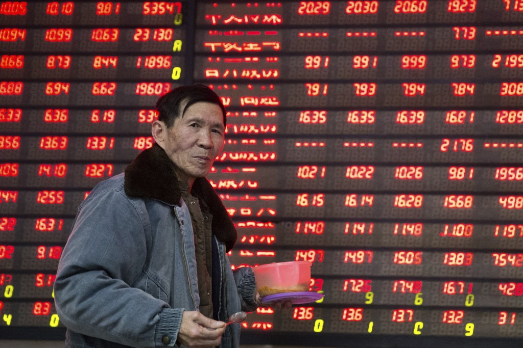 An investor walks past an electronic screen showing stock information at a brokerage house in Nanjing, Jiangsu province, China January 14, 2016. China's yuan currency slipped despite the efforts of the authorities on Thursday, as the gloom in global markets obscured signs that China's economy may not be weakening as fast as some investors had feared. REUTERS/China Daily ATTENTION EDITORS - THIS PICTURE WAS PROVIDED BY A THIRD PARTY. THIS PICTURE IS DISTRIBUTED EXACTLY AS RECEIVED BY REUTERS, AS A SERVICE TO CLIENTS. CHINA OUT. NO COMMERCIAL OR EDITORIAL SALES IN CHINA.