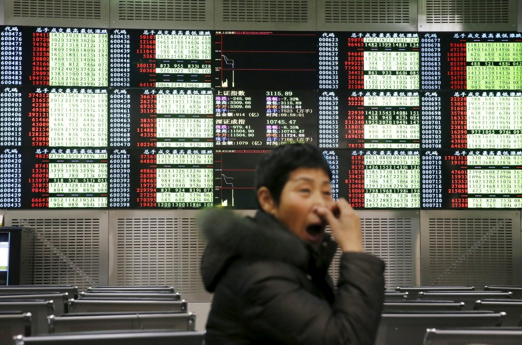 An investor yawns in front of an electronic board showing stock information, after the new circuit breaker mechanism suspended today's stocks trading, in Shanghai, China, January 7, 2016. REUTERS/China Daily ATTENTION EDITORS - THIS PICTURE WAS PROVIDED BY A THIRD PARTY. THIS PICTURE IS DISTRIBUTED EXACTLY AS RECEIVED BY REUTERS, AS A SERVICE TO CLIENTS. CHINA OUT. NO COMMERCIAL OR EDITORIAL SALES IN CHINA.