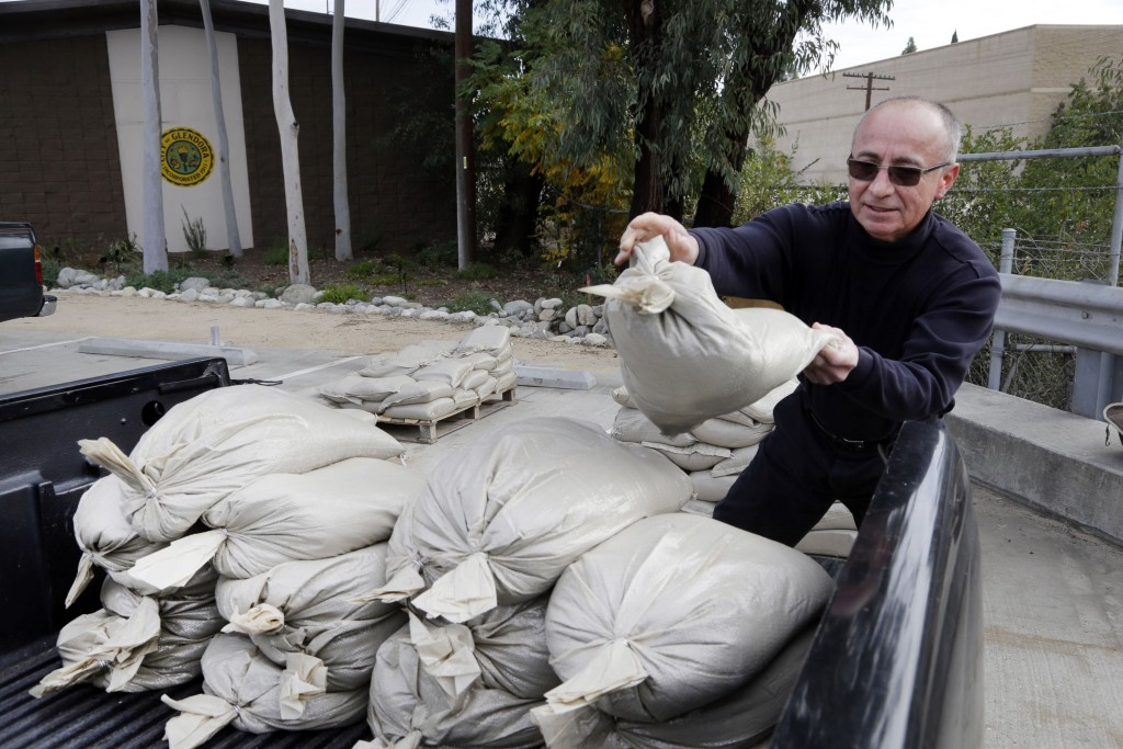 Glendora resident Frank Salazar stockpiles sandbags to protect his home from flooding in Glendora, Calif., Monday, Jan. 4, 2016. After all the talk, El Niño storms have finally lined up over the Pacific and started soaking drought-parched California with rain expected to last for most of the next two weeks, forecasters said Monday. (AP Photo/Nick Ut)
