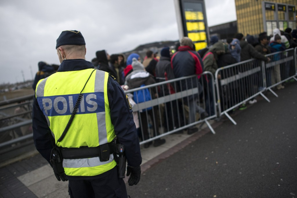A police officer keeps guard as migrants arrive at Hyllie station outside Malmo, Sweden. Picture taken November 19, 2015. REUTERS/Johan Nilsson/TT NEWS AGENCY ATTENTION EDITORS - THIS IMAGE WAS PROVIDED BY A THIRD PARTY. FOR EDITORIAL USE ONLY. NOT FOR SALE FOR MARKETING OR ADVERTISING CAMPAIGNS. THIS PICTURE IS DISTRIBUTED EXACTLY AS RECEIVED BY REUTERS, AS A SERVICE TO CLIENTS. SWEDEN OUT. NO COMMERCIAL OR EDITORIAL SALES IN SWEDEN. NO COMMERCIAL SALES.