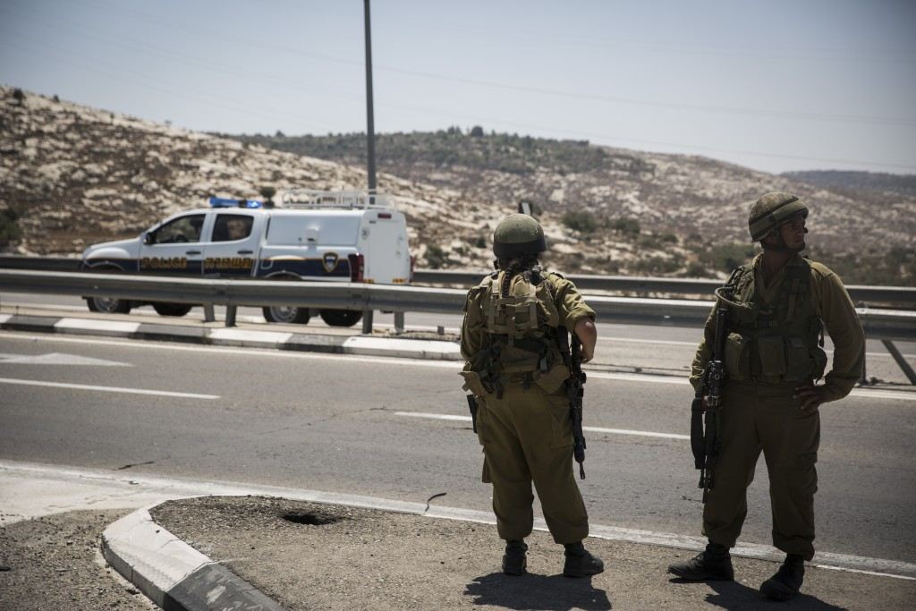 FILE - Israeli soldiers and security at the scene where a Palestinian man stabbed a soldier, lightly injuring him, at the 'Bell' Checkpoint, on road 443 near Beit Horon, on August 15, 2015. (Hadas Parush/Flash90)