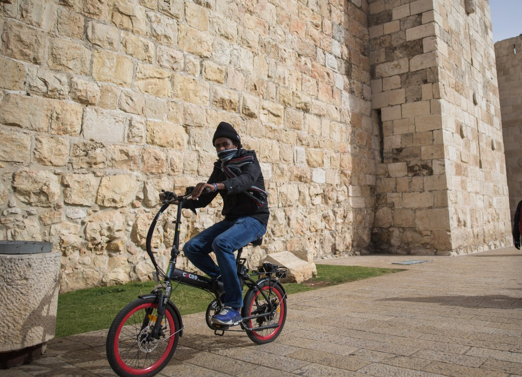A man rides his bicycle near the Old City. Photo by Yonatan Sindel/Flash90