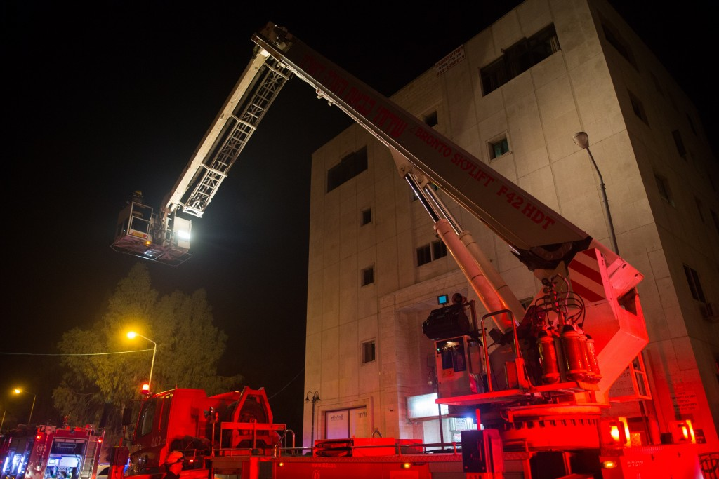 "Firefghters stand at the entrance to a building where the offices of the left-wing NGO ""B'Tselem"" is located, in Jerusalem on January 10, 2016, A major fire broke out late Sunday at the offices of the left-wing NGO ""B'Tselem"", Police investigate if it was an Arson attack. (Yonatan Sindel/Flash90)"