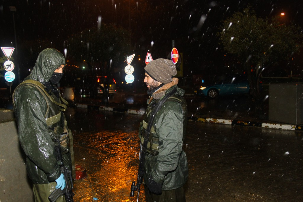 Israeli soldiers stand guard in the cold near the Gush Etzion junction on Janaury 24, 2016, as a major winter storm hits the country. (Gershon Elinson/Flash90)