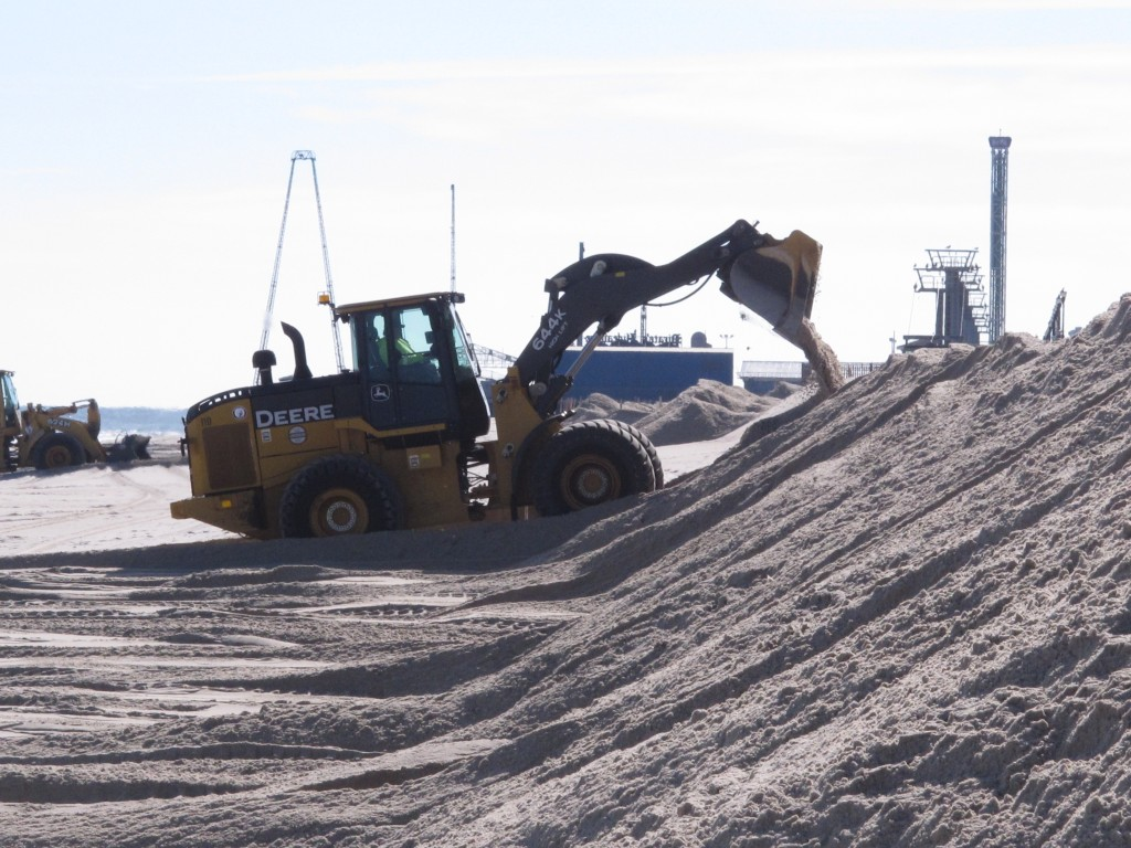 Front-end loaders dump sand into temporary barriers on a beach in the Ortley beach section of Toms River, N.J., Thursday, as a major coastal storm approached. (AP Photo/Wayne Parry)