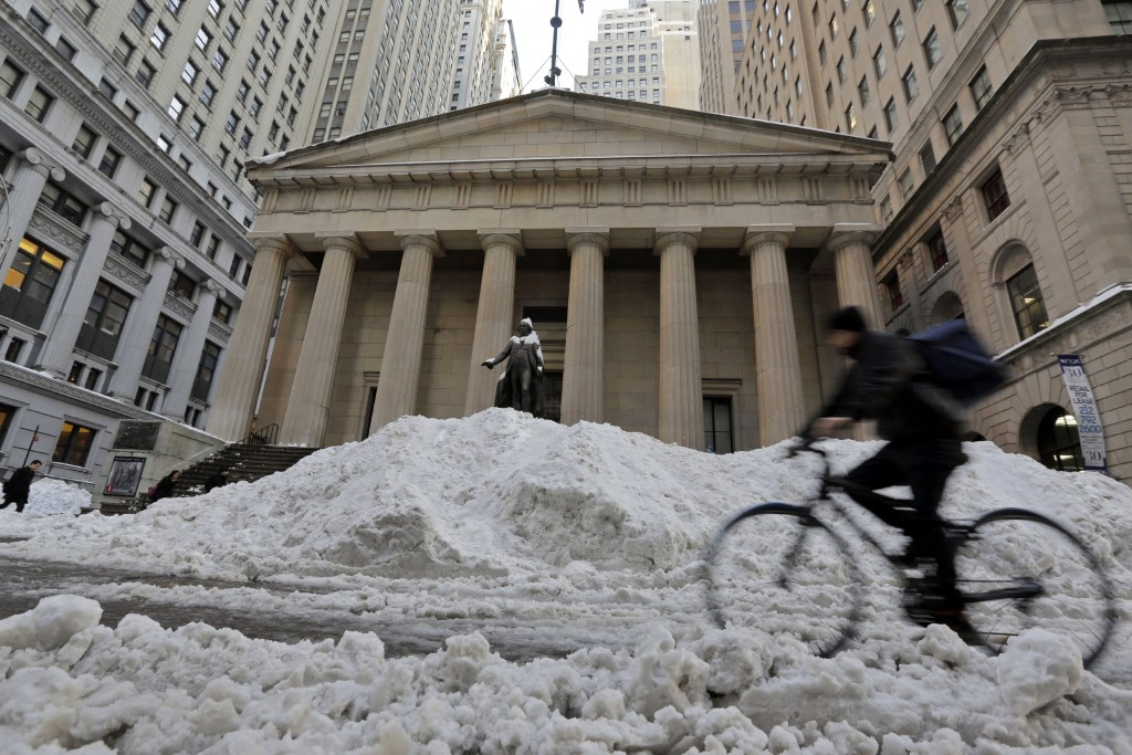 A bicyclist rides on Wall Street in front of Federal Hall in New York's Financial District, Monday. (AP Photo/Richard Drew)