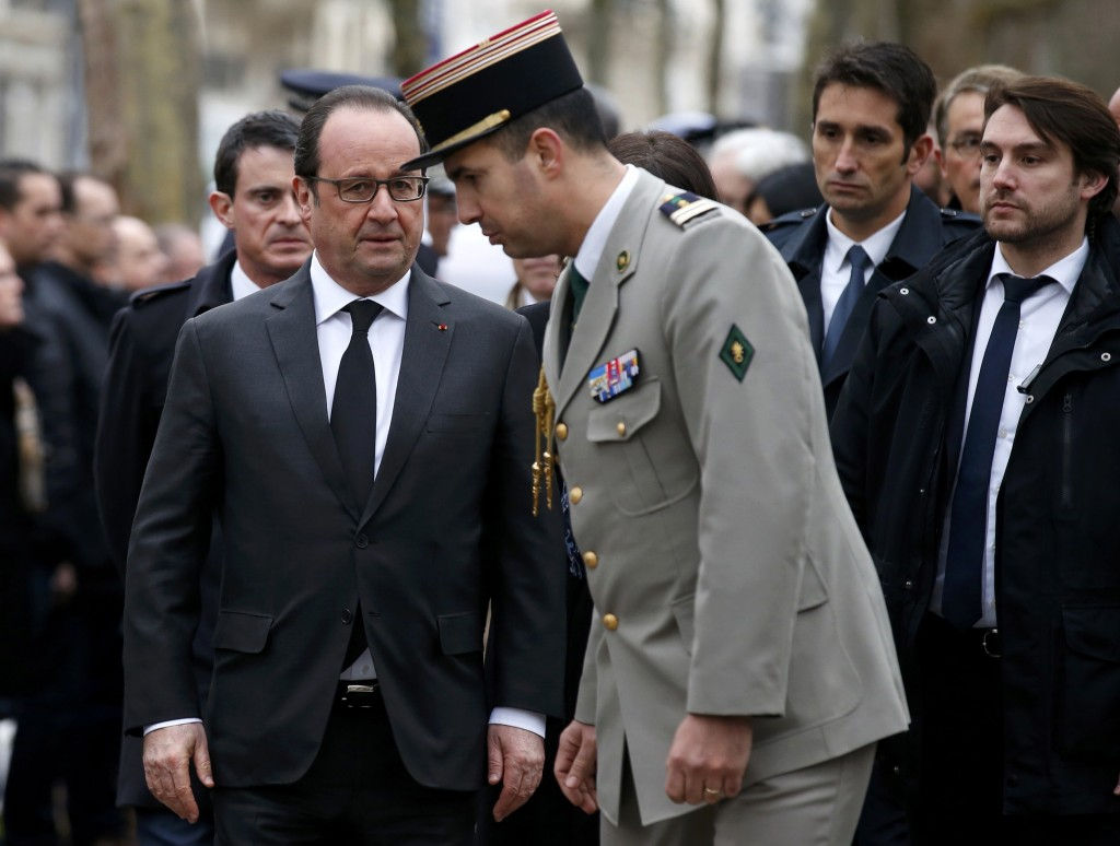 French President Francois Hollande (C) speaks with officials during a ceremony to unveil a commemorative plaque at the site where policeman Ahmed Merabet was killed during the last year's January attack in Paris, France, January 5, 2016. France this week commemorates the victims of last year's Islamist militant attacks on satirical weekly Charlie Hebdo and a Jewish supermarket with eulogies, memorial plaques and another cartoon lampooning religion. REUTERS/Benoit Tessier