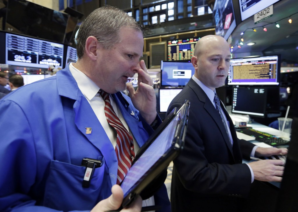 Trader Michel Conlon, left, and specialist Jay Woods work on the floor of the New York Stock Exchange on Monday. (AP Photo/Richard Drew)